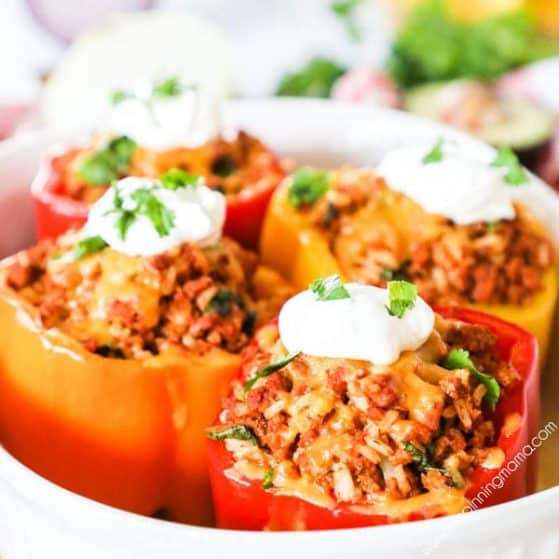 Mexican Stuffed Peppers topped with sour cream and cilantro
