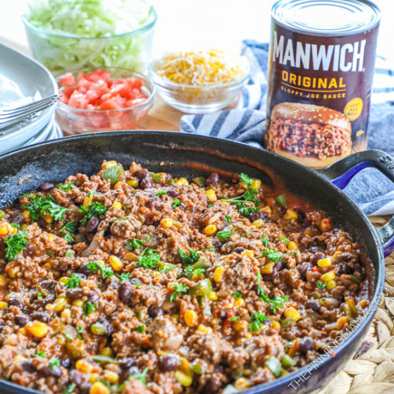 Ground Beef Sloppy Joes on a table with Manwich and toppings