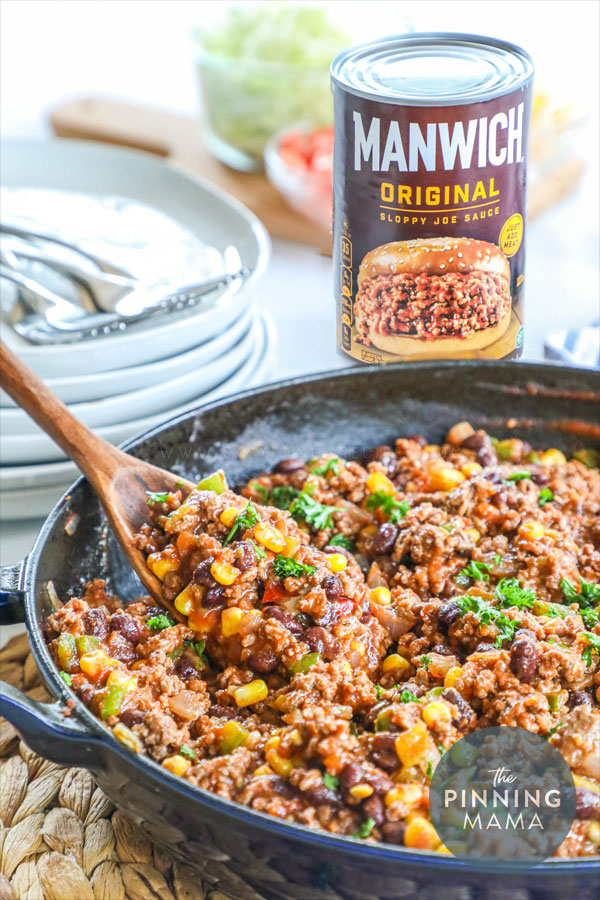 Serving ground beef sloppy joes from a skillet with a wooden spoon