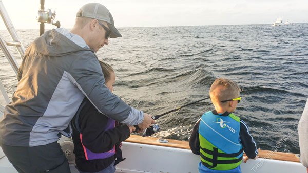 Dad with kids on a deep sea fishing charter